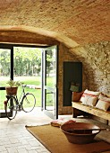 Bicycle and wooden bench in front of open glass door in vaulted foyer