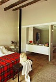View past red tartan blanket on bed into ensuite bathroom with simple fitted shelving