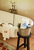 Vintage bath taps on free-standing white bathtub, monogrammed towels and zinc bucket on stool