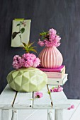 Pink cherry blossom in pastel vases with structured surfaces