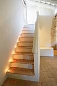Mit Teelichtern und Rosenblütenblättern romantisch dekorierte Treppe in restauriertem historischem Gebäude