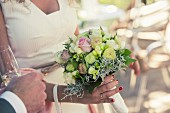 Braut hält Brautstrauss