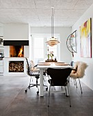 Various dining chairs and fire in open fireplace in open-plan kitchen