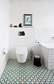Toilet and bathtub in bathroom with green and white patterned floor tiles