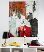 Modern artwork on wall anove designer table lamp, toy car and figurine on top of shelves