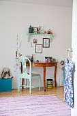 Turquoise chair in front of semi-circular desk in child's bedroom