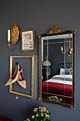 Shoes in frame on wall and old mirror above semi-circular table