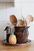Küchenutensilien in einem rustikalen Tontopf und eine Deko-Ananas