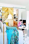 Frau zündet Kaminfeuer an, Blick von Wohnbereich mit rustikaler Schiebetür in Küche