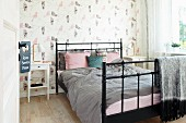 Black metal bed with grey and dusky pink bed linen against wall with bird-patterned wallpaper