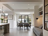 Open-plan interior with white floor, dining area and sofa in niche
