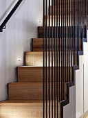 Modern wooden staircase with iron-rod balustrade and spotlights