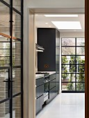 View into kitchen with black fronts and floor-to-ceiling windows