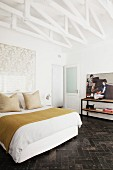 Schlafzimmer mit weiß gestrichenen Fachwerkträgern und Retro Flair