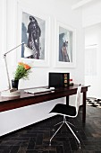 Laptop on exotic-wood table and designer chair below large photos