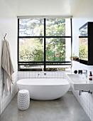 Free-standing bathtub and window with black frame in bright minimalist bathroom