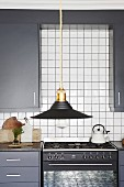 Black lampshade in front of grey fitted kitchen with white wall tiles and gas cooker