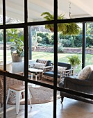 Roofed furnished terrace and summer garden seen through industrial glazing