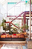 Orange scatter cushions on couch in comfortable lounge area in front of staircase in loft apartment with glass façade