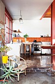 Recycled parquet floor and orange wall tiles in open-plan kitchen of loft apartment