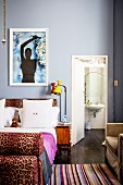 Bed with leopard-print elements against pale blue wall and view into bathroom