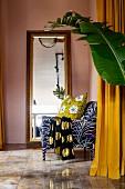 Gemusterter Sessel vor Bodenspiegel, im Vordergrund ein Blatt