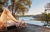 Lounger under mosquito net on edge of pool with panoramic view