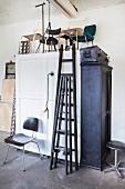 Schwarze Leitern und verschiedene Stühle auf weißem Holzschrank in aufgeräumter Werkstatt