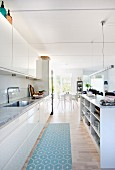 Open-plan kitchen with white glossy fronts and island counter
