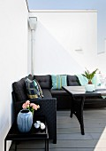 Black corner sofa with colourful scatter cushions against white wall on summery terrace