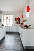 Simple white fitted kitchen with granite worksurface and red retro pendant lamps