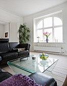 Leather couch and glass table in lounge area of renovated period apartment