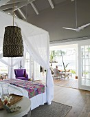 View past canopy bed onto terrace of summery beach house
