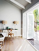 Table lamps on console table and view of terrace and garden through open door
