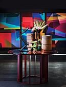 Runder Tisch mit Deko-Accessoires vor abstrakter Kunst