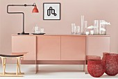 Glass vases and anglepoise lamp on pink sideboard