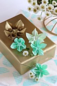 Origami flowers on gift wrapped in gold paper
