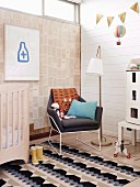 Children's room with white wood paneling, designer armchair and window ribbon