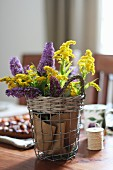 Wire basket of yellow and purple flowers decorating table