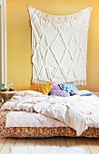 Cream fringed rug hung on yellow wall above bed