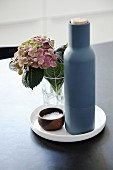 Blue bottle, hydrangea and salt cellar on white plate