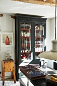 Crockery in glass-fronted cabinet in vintage interior