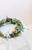 Wreath of twigs and succulents on white wooden stool