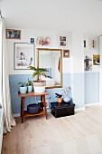 Plants on side table below pictures on wall with pale blue dado
