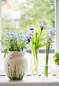 Three vases of delicate flowers on windowsill