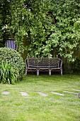 Gartenbank vor Lattenzaun unter Baum in Garten