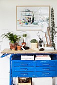Plant arrangement and table lamp on top of blue vintage workbench below framed picture