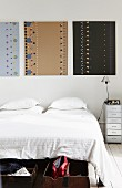 Three artworks with patterns of dots above bed
