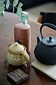 Oriental iron teapot, milk jugs and pot