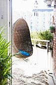 Comfortable wicker hanging chair on summery balcony